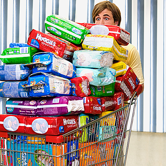 Man pushing shopping cart filled with diapers