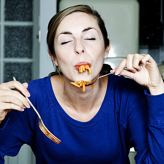 Woman enjoying mouthful of pasta