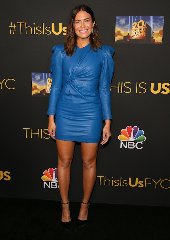 Mandy Moore wears a blue leather-looking mini dress with knotted details and puffed shoulders