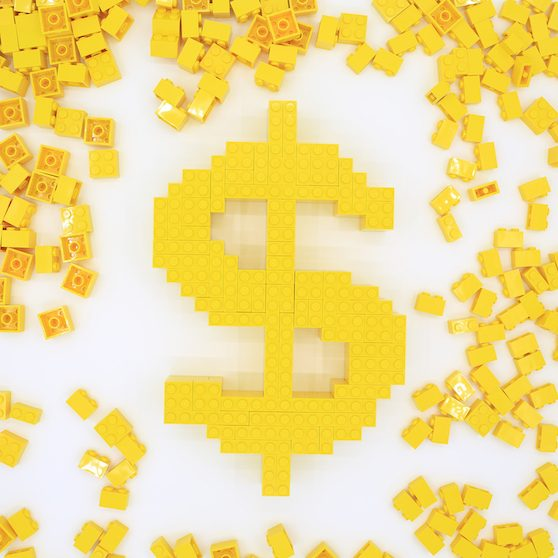 Yellow Lego bricks stacked to create the symbol for money