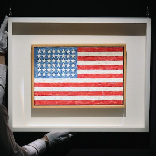 "The ""Flag"" painting by Jasper Johns being handled by an employee at an auction"