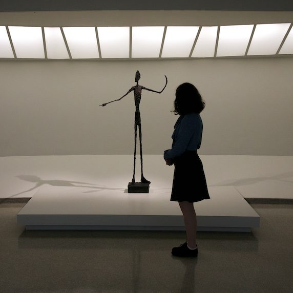 "A woman in silhouette looks into the Alberto Giacometti sculpture ""Pointing Man"" at an exhibit"
