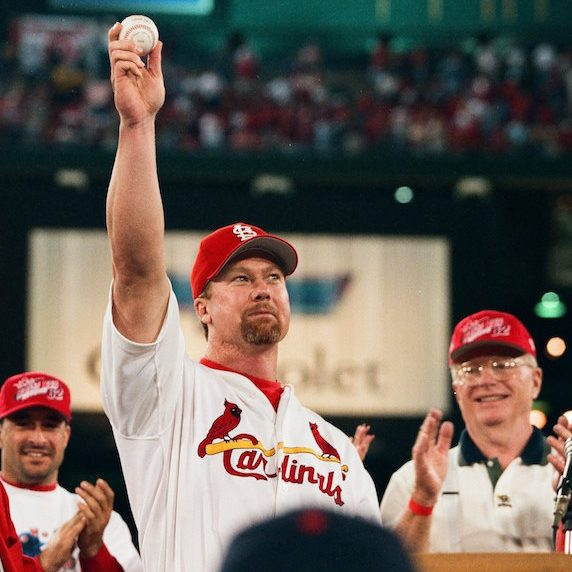 Mark McGwire extends his arm in celebration after a game, holding in his hand the game baseball