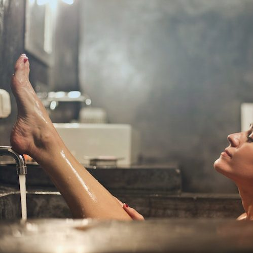 Woman with her feet lifted in a bathtub