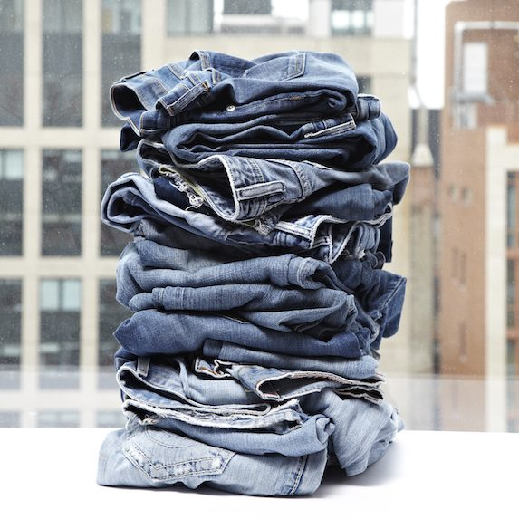 Pile of jeans by a city window