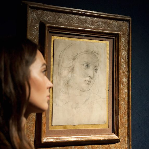 A woman poses by a rare drawing by Raphael at a Christie's auction