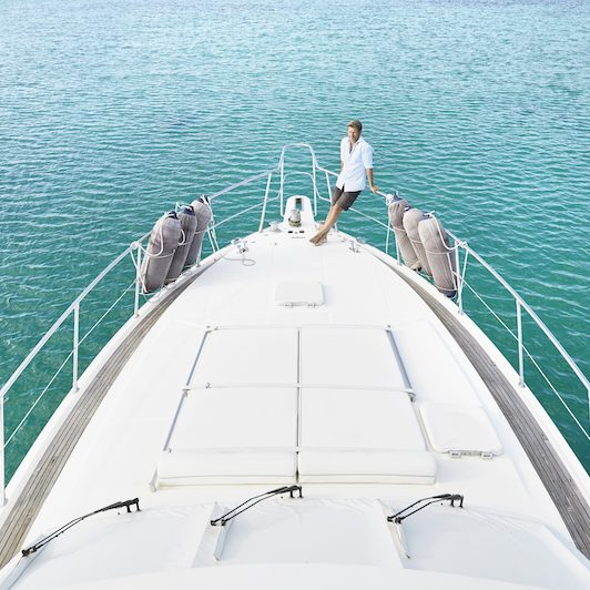 Man stands on the deck of a luxury yacht