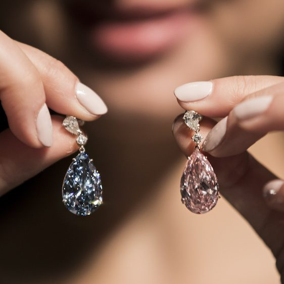 A woman holds up a pair of mismatched diamond earrings