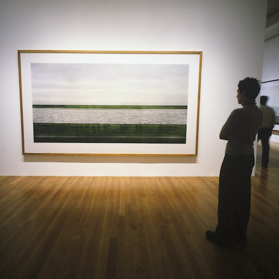 A woman stands looking at a photo by Andreas Gursky on display