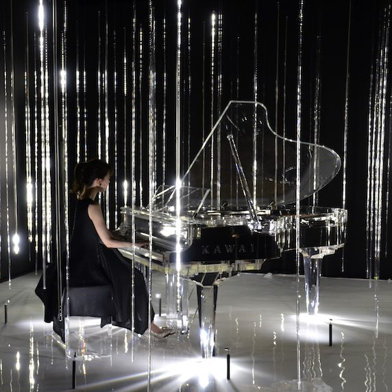 A woman sits and plays at a crystal piano