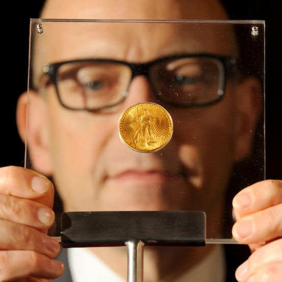 CEO of the London Mint examines a glass-encased 1933 Double Eagle coin