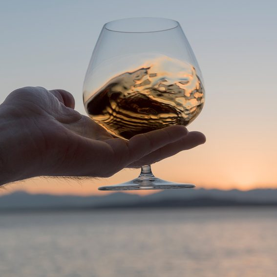 Man holds a glass of cognac up against an ocean backdrop at sunset