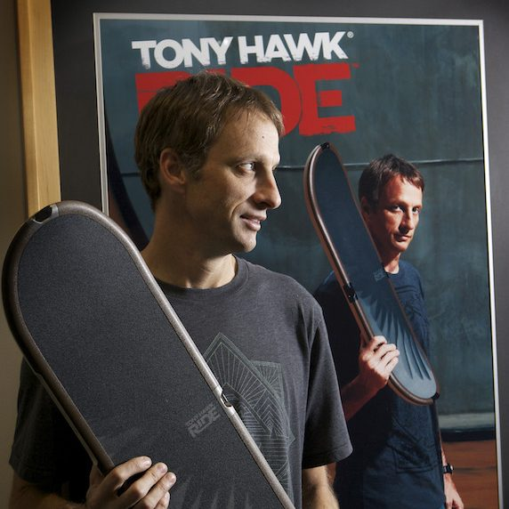 Tony Hawk stands in front of a promotional image for his skateboard video game