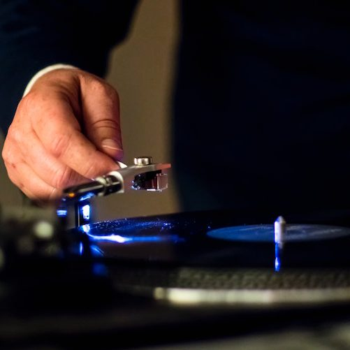 A man moves the arm on a high-tech turntable