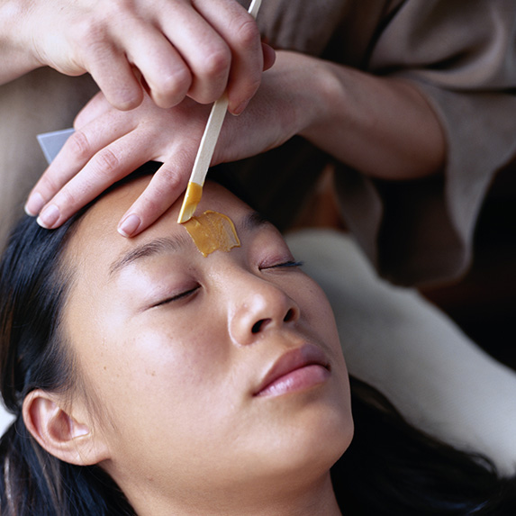 woman getting eyebrows professionally waxed