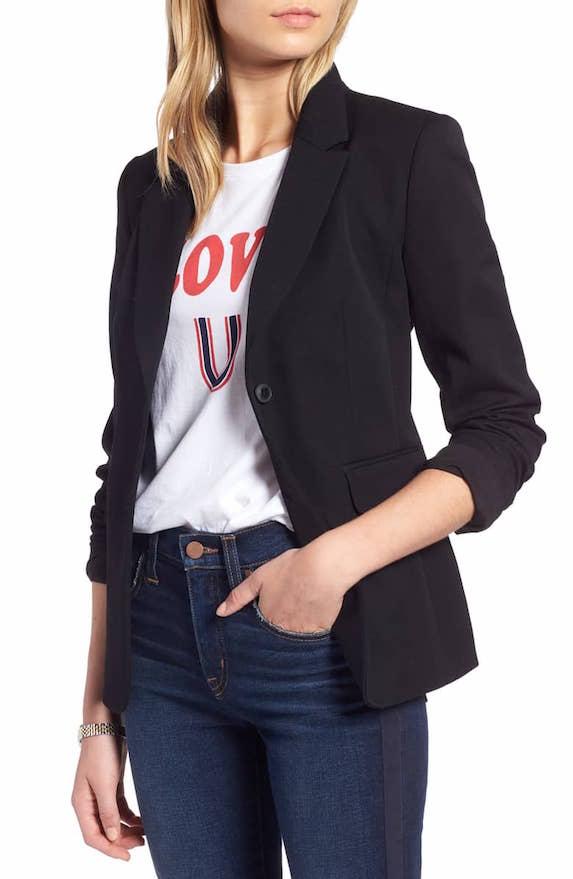 Model wears jeans, t-shirt and blazer