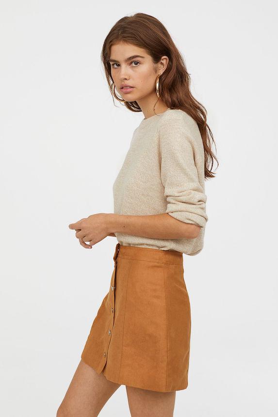 Model wears mini skirt and knit sweater