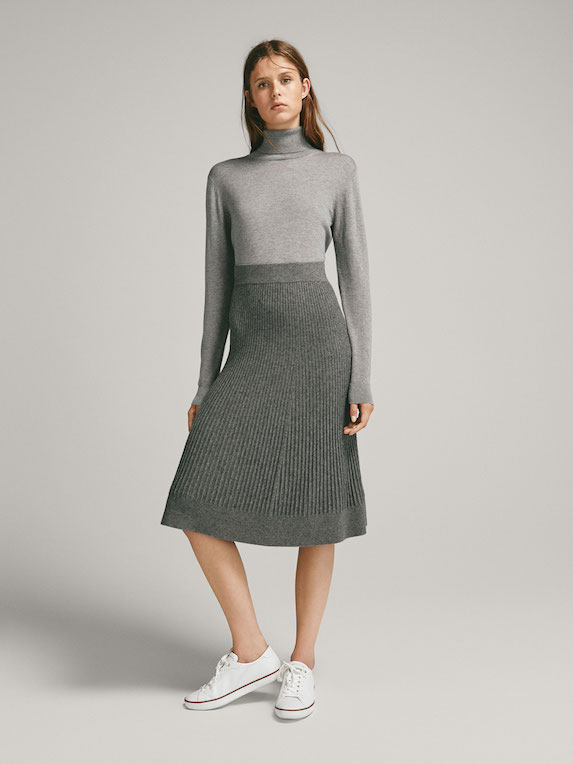 Model wears grey knit and skirt