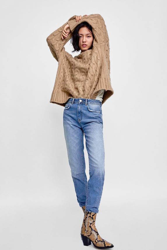 Model wears ankle boots, jeans and a chunky knit sweater