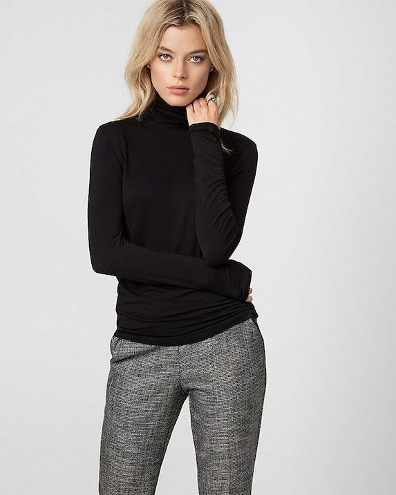 Model wears black turtleneck and structured pants
