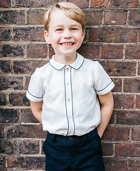 Prince George smiling against a brick wall