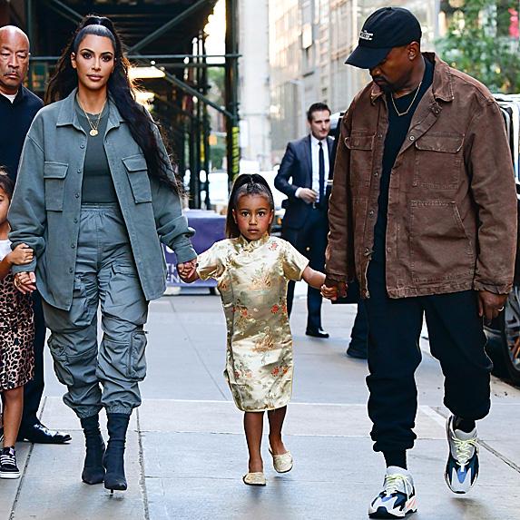 Kim Kardashian, daughter North and Kanye West walking down street