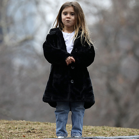 Penelope Disick standing outside in park