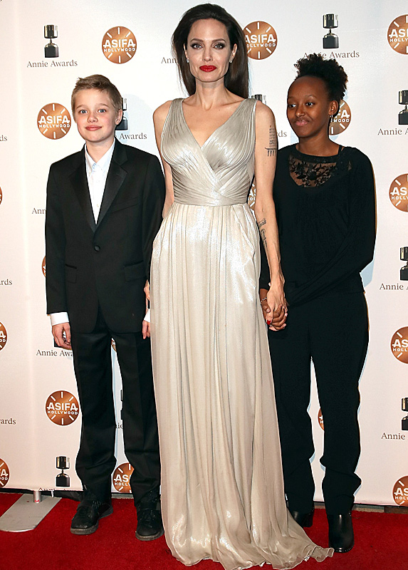 Angelina Jolie standing between daughters Shiloh and Zahara on red carpet