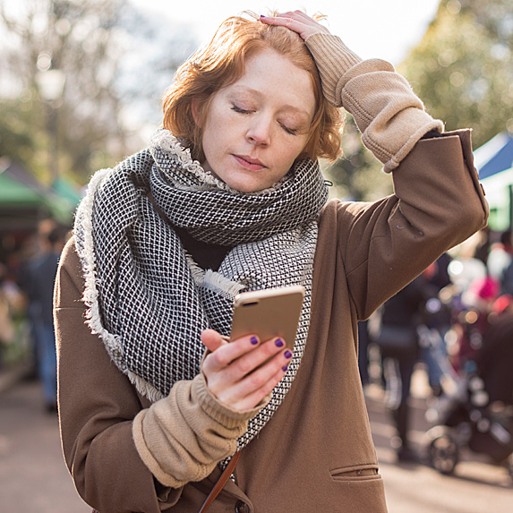 Upset woman outside looking at phone
