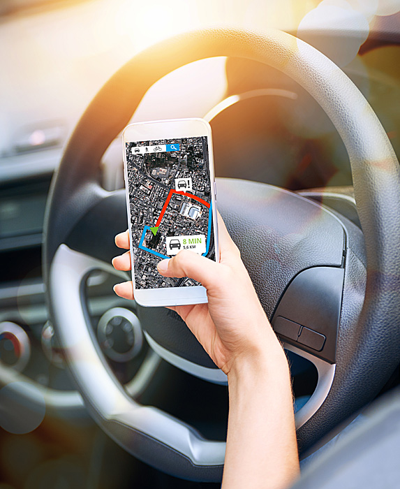 Woman holding phone with navigation open on screen