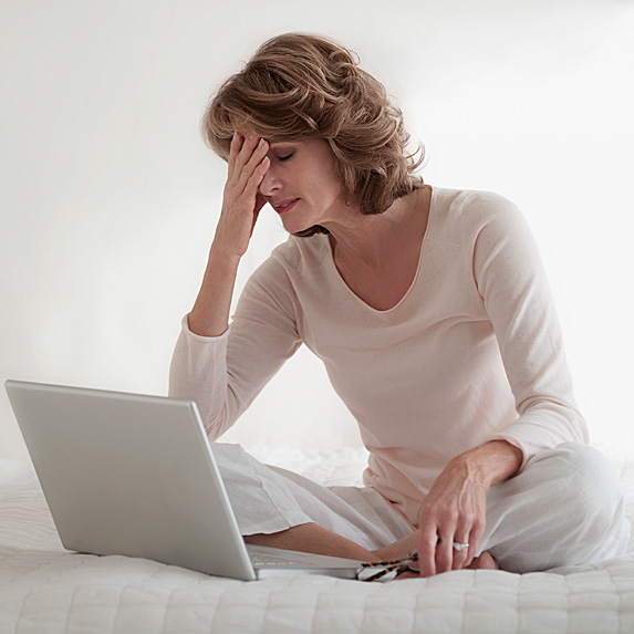 Woman sitting on bed with hand to forehead, laptop open in front of her