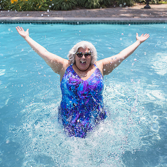 senior woman jumping out of water in pool