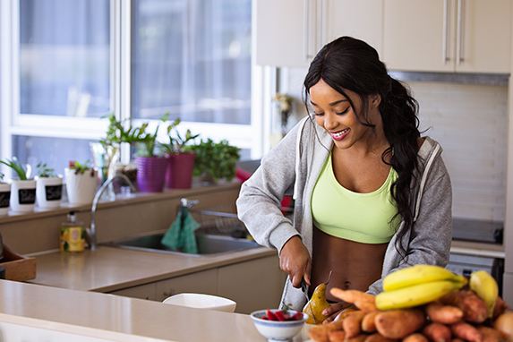 woman smiling and making healthy snack