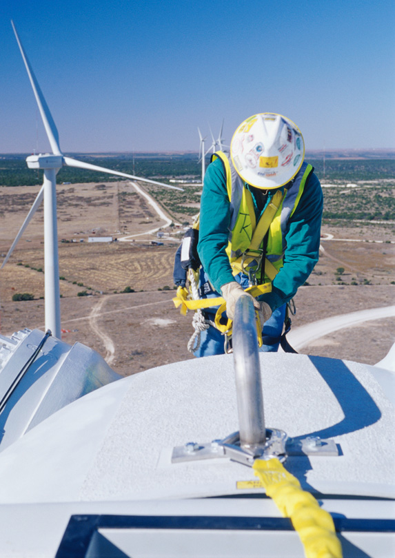 Wind turbine service technician on top of a turbine