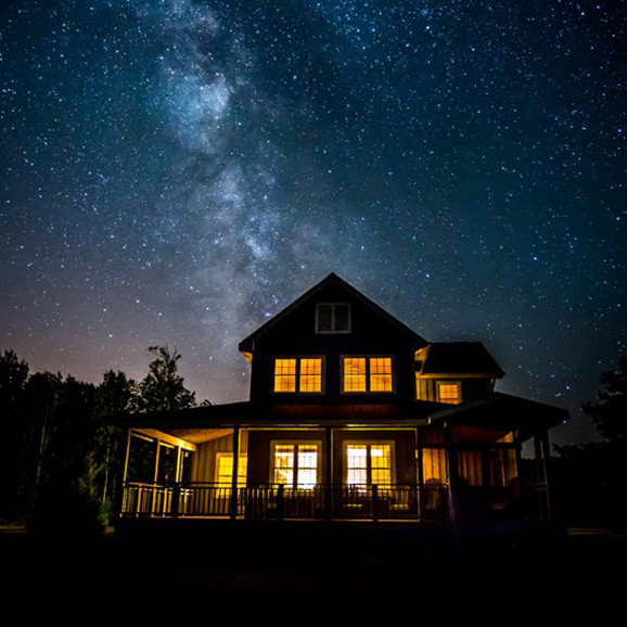 House lit up from inside, against a starry sky
