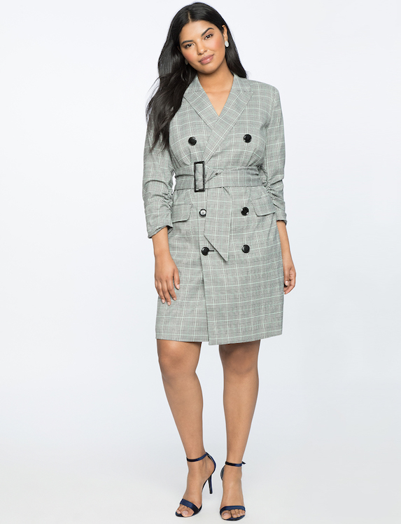 Model wears a check-print belted blazer dress from fashion label Eloquii