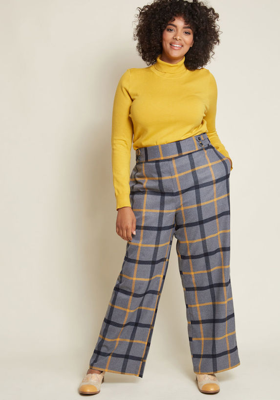 Model wears yellow turtleneck and wide-leg check-print pants