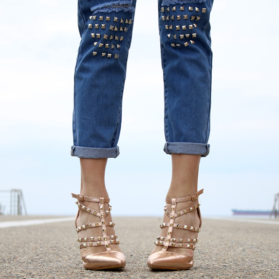 Woman wearing studded gold heels and jeans