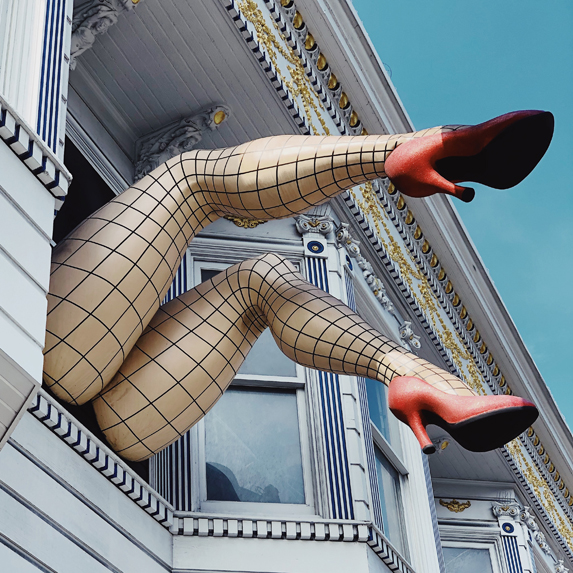 Woman dangling high heels out the window
