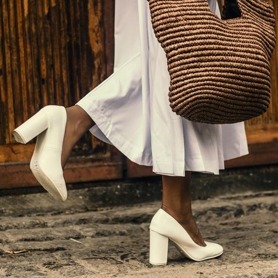 Woman walking down street in chunky white heel