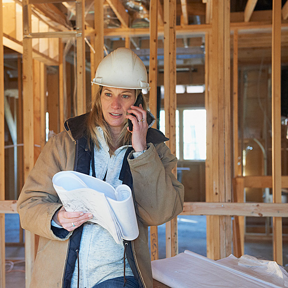 Woman wearing hardhat on phone in building under construction