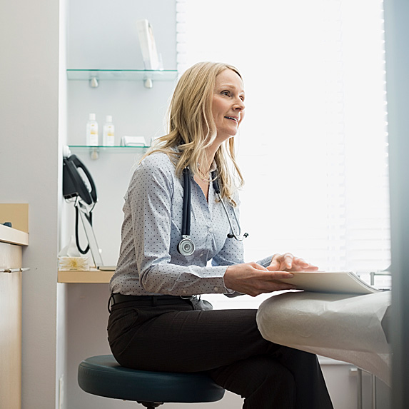 Woman with stethoscope around neck sitting in patient room