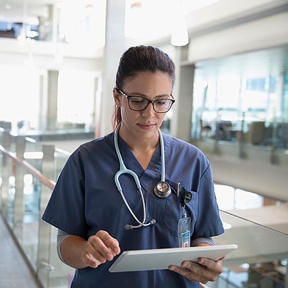 Female nurse practitioner looking at tablet