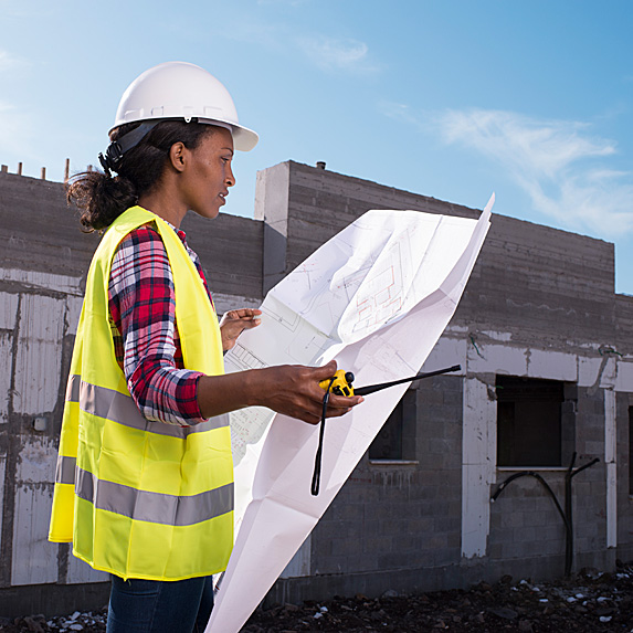 Woman looking at blueprints outside building under construction