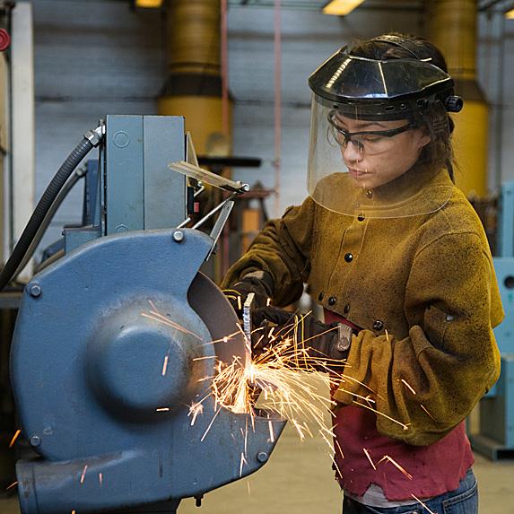 Woman using welding machinery