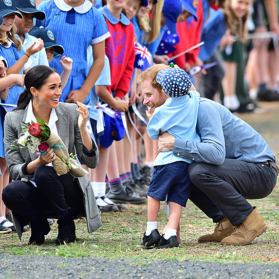Meghan smiling as boy hugs Harry
