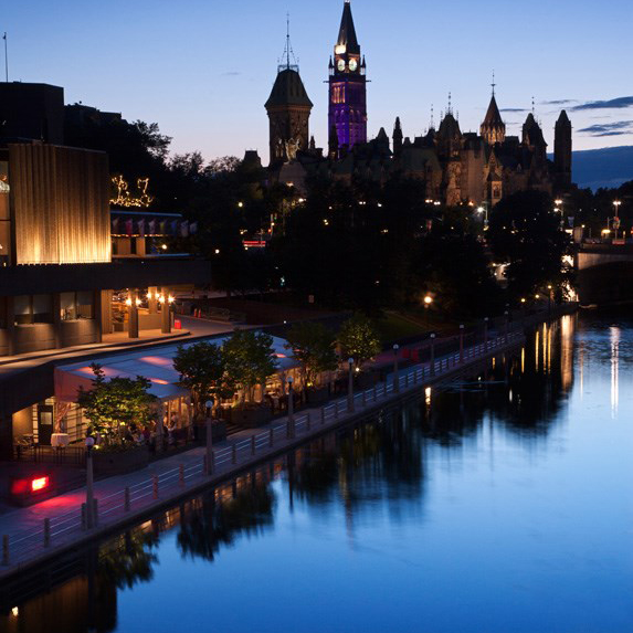Shot of the lovely Rideau Canal at dusk with lights speckled in the background