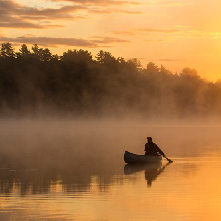 Sunset shot of a person in their canoe, with the golden light reflecting off the water