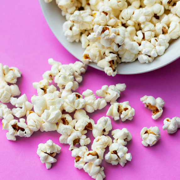 Popcorn in a white bowl, pink background.