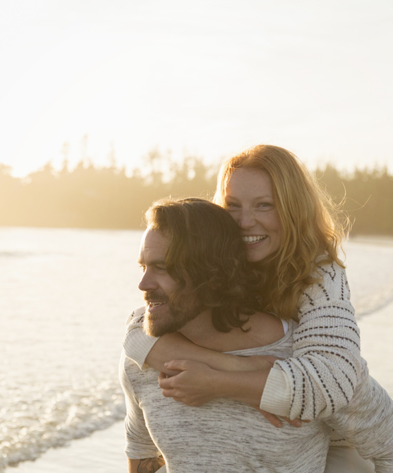 Smiling couple piggybacking on the beach